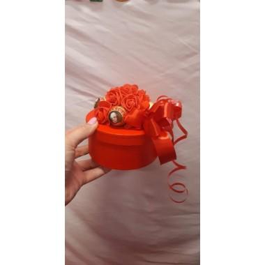 Piros ajándékdoboz csokoládéval díszítve